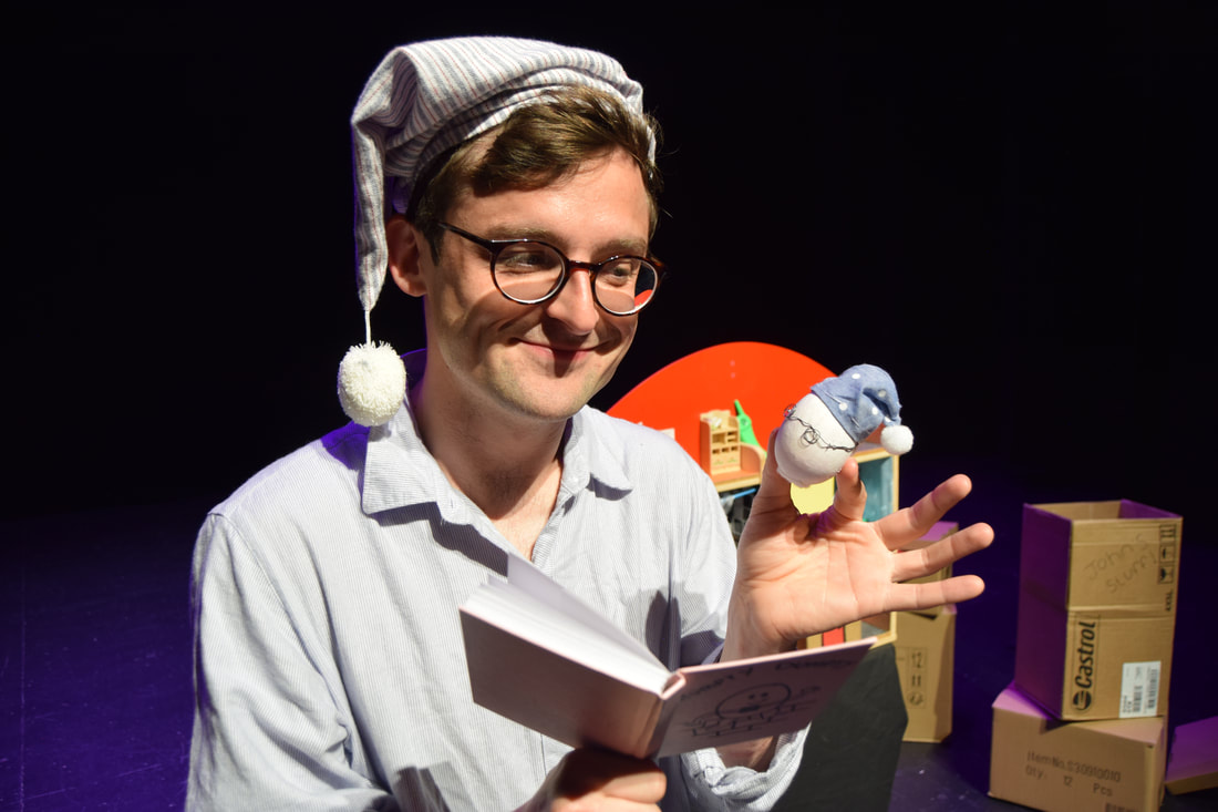 Production image from GOODNIGHT EGG. A man wearing glasses, dressed in a blue nightshirt and striped blue nightcap holds a book in one hand and a white egg in the other. The white egg is also wearing tiny glasses and a tiny blue nightcap. In the background, there are cardboard moving boxes. A wooden model house can be partially seen behind the man.